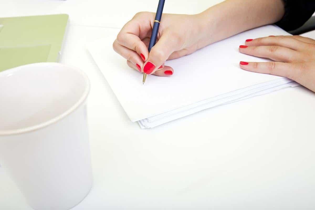 kobieta pisze długopisem na czestej kartce papieru