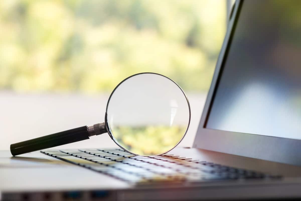 lupa leżąca na klawiaturze laptopa