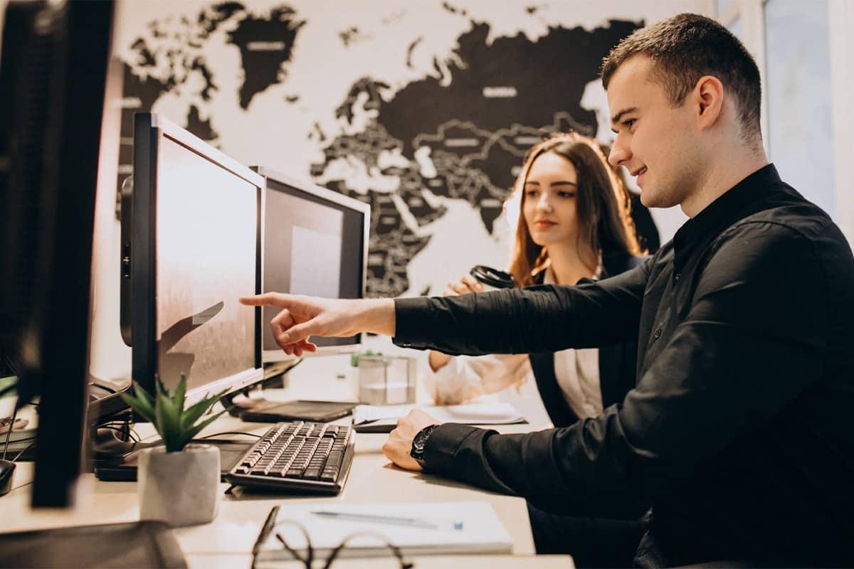 młody mężczyzna przed monitorem wskazuje palcem na monitor i pokazuje coś siedzącej obok młodej kobiecie