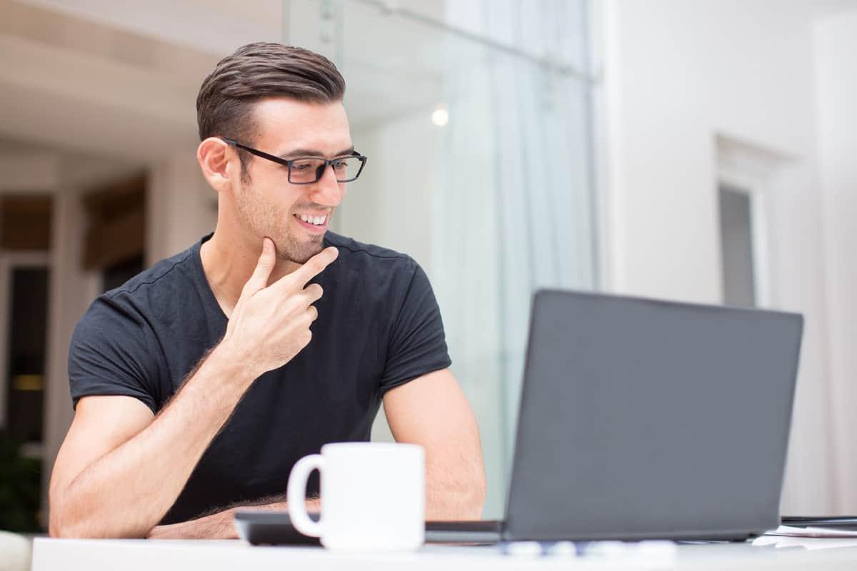 młody uśmiechnięty mężczyzna siedzący przed laptopem